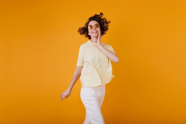 Chica pálida con expresión de la cara de éxtasis disfrutando de la sesión de fotos en traje de verano blanco. mujer joven complacida en camiseta amarilla sonriendo mientras posa en la pared naranja.