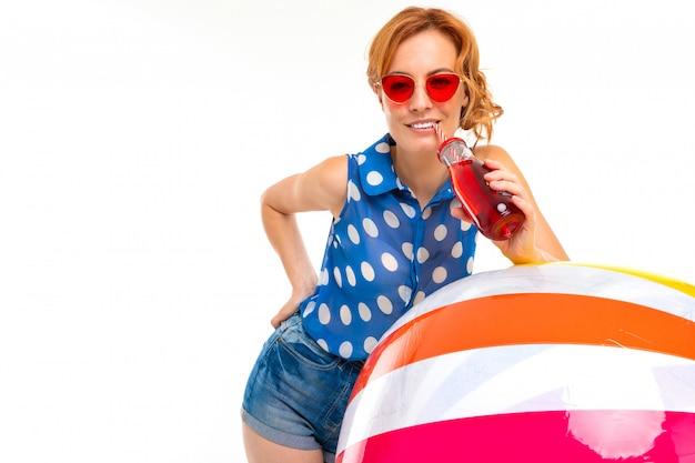 Chica en pantalones cortos y una camiseta bebe un cóctel y se inclina sobre una pelota inflable en blanco