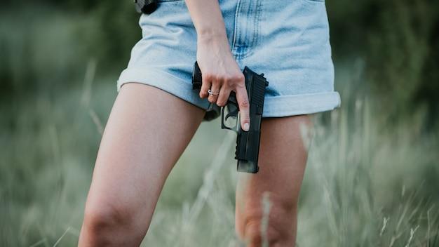 Chica en pantalones cortos de mezclilla y con una pistola en la mano posando en el campo. de cerca