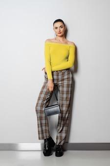 Chica en pantalones a cuadros y suéter amarillo con bolso pequeño posando cerca de la pared blanca