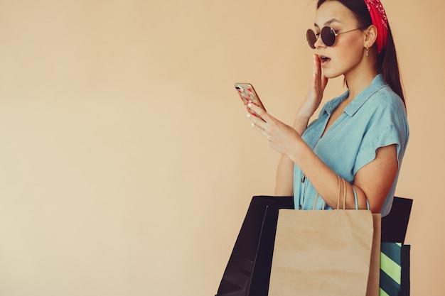 Chica en una pared amarilla con bolsas de compras