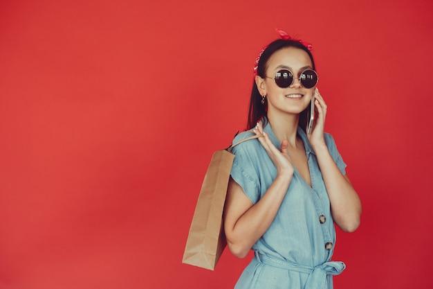 Chica en una pared roja con bolsas de compras