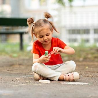 Chica en el parque dibujando con tiza