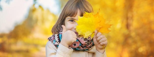 Chica en el parque con hojas de otoño.