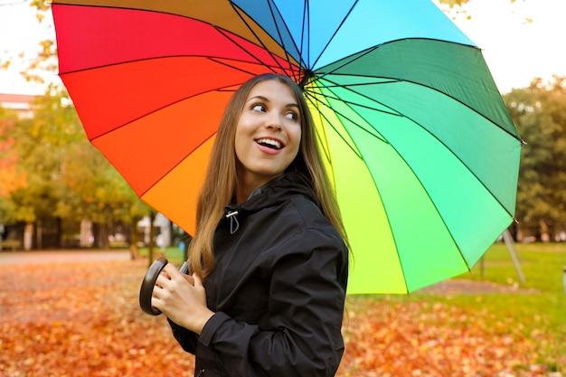 Chica en el parque con impermeable y paraguas en otoño