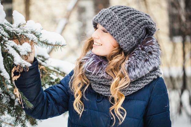 Chica en el parque de invierno cubierto de nieve