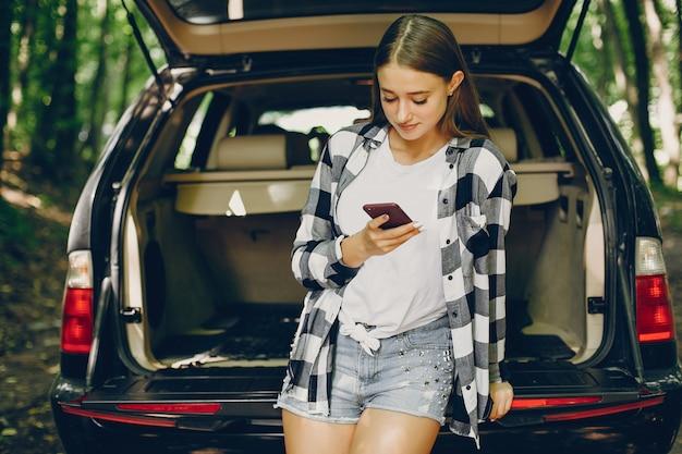 Chica en un parque de verano cerca del coche