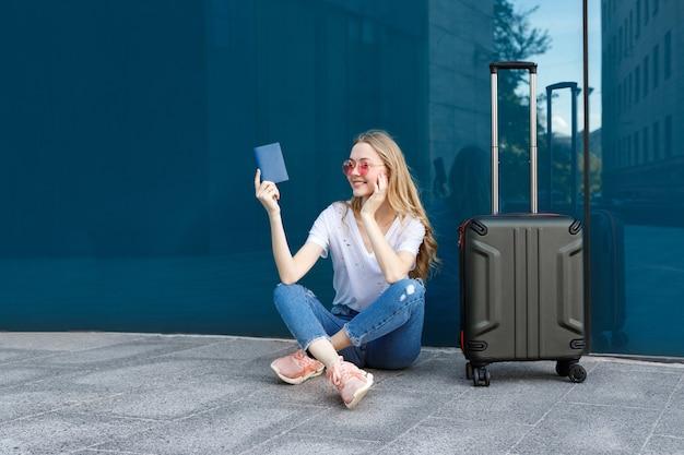 Chica con pasaporte, equipaje y gafas cerca de la ventana.