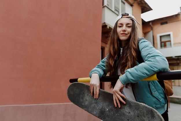 Chica patinadora al aire libre y su patineta