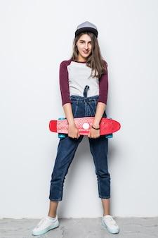 Chica patinadora moderna sosteniendo patineta roja en sus manos aisladas en la pared blanca