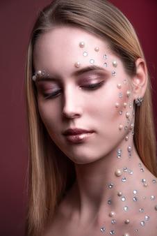 Chica con pedreria blanca y perla en su cara.