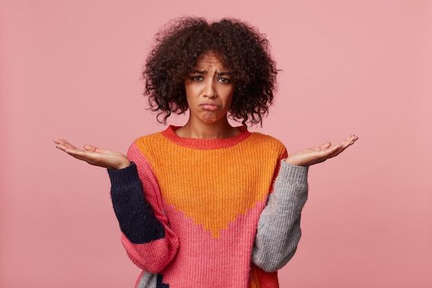 Chica con peinado afro que parece indefenso ofendido triste malestar, de mal humor, de pie con las palmas levantadas sosteniendo un espacio de copia, frunció los labios, siente injusticia desesperanza, aislado en rosa