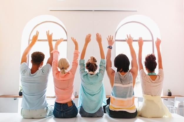 Chica con peinado de moda sentada con las manos en alto junto a sus amigos de la universidad y mirando a la ventana grande. estudiantes felices divirtiéndose en la habitación luminosa después de los exámenes.