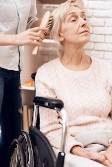 Chica peinando a una anciana en casa