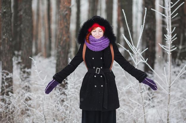 La chica pelirroja con abrigo se regocija en el invierno, el hombre se para en la nieve, la niña en el bosque de invierno, la gente se ríe, se alegra, el buen humor, la felicidad, la niña se ríe