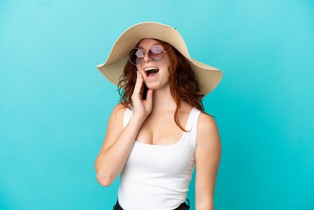 Chica pelirroja adolescente aislada sobre fondo azul en traje de baño en vacaciones de verano con expresión de sorpresa