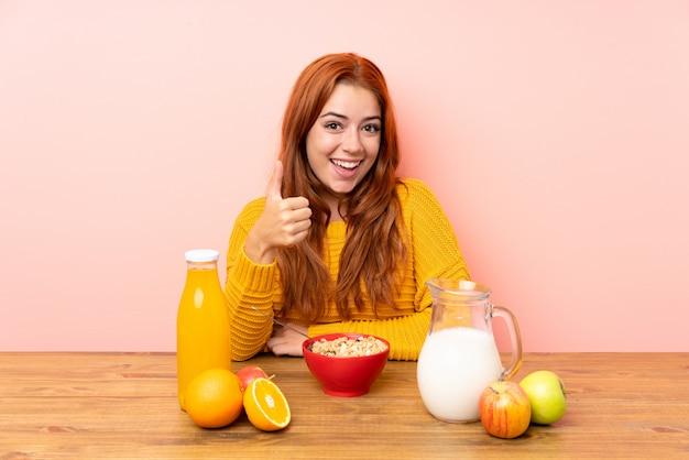 Chica pelirroja adolescente desayunando en una mesa dando un gesto de pulgares arriba