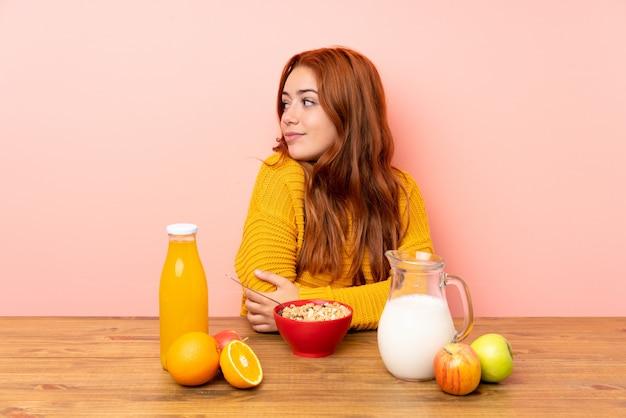 Chica pelirroja adolescente desayunando en una mesa riendo