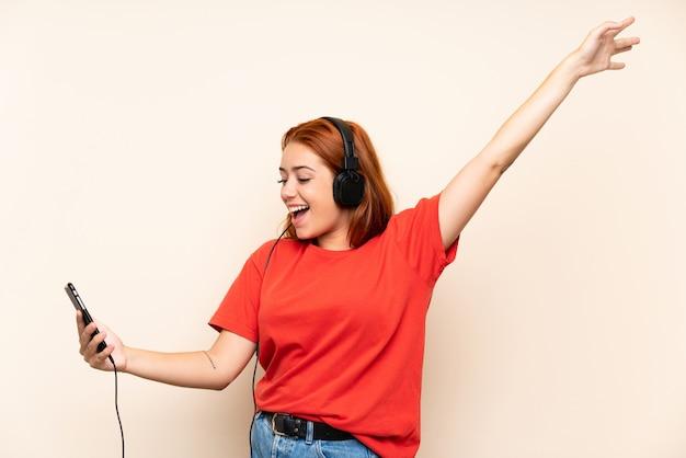 Chica pelirroja adolescente escuchando música con un móvil sobre pared aislada