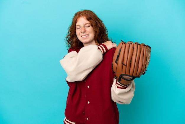 Chica pelirroja adolescente con guante de béisbol aislado sobre fondo azul que sufre de dolor en el hombro por haber hecho un esfuerzo