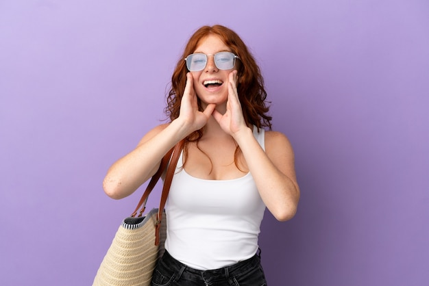 Chica pelirroja adolescente sosteniendo una bolsa de playa aislada sobre fondo púrpura gritando y anunciando algo