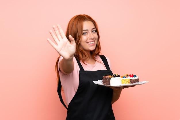 Chica pelirroja adolescente sosteniendo un montón de diferentes mini pasteles sobre saludos aislados con la mano con expresión feliz
