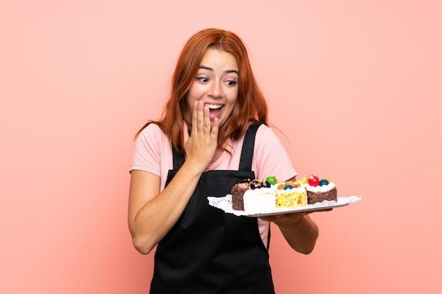 Chica pelirroja adolescente sosteniendo muchos mini pasteles diferentes sobre pared rosa aislada con expresión facial de sorpresa y sorpresa