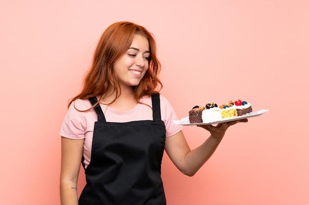 Chica pelirroja adolescente sosteniendo muchos mini pasteles diferentes sobre rosa aislado con expresión feliz