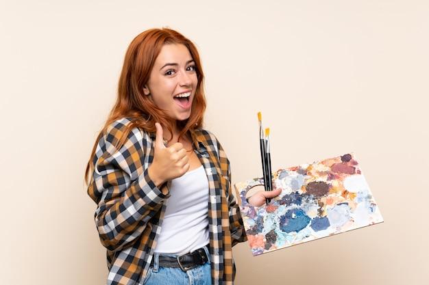Chica pelirroja adolescente sosteniendo una paleta dando un gesto de pulgares arriba