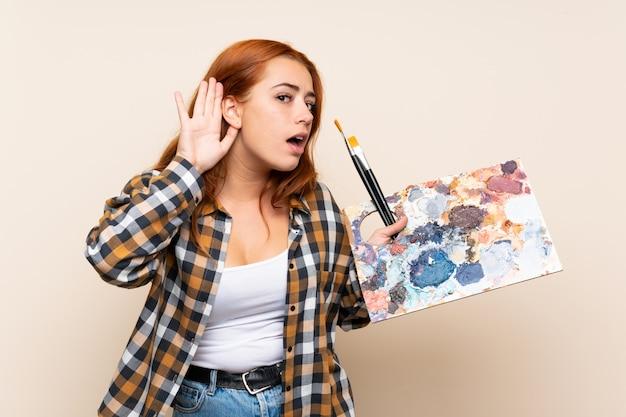 Chica pelirroja adolescente sosteniendo una paleta escuchando algo