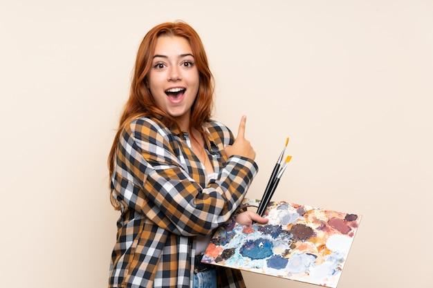Chica pelirroja adolescente sosteniendo una paleta sobre dedo señalador aislado al lado