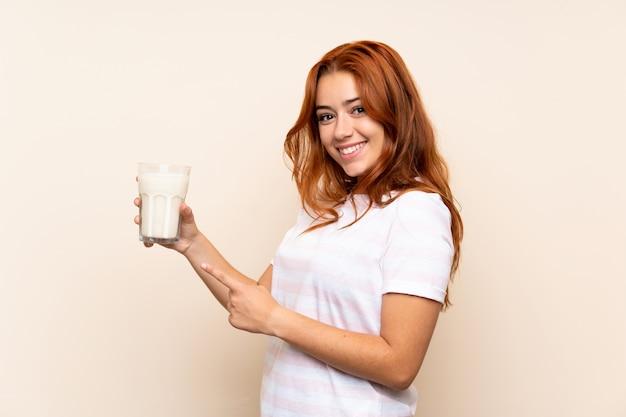 Chica pelirroja adolescente sosteniendo un vaso de leche y apuntando