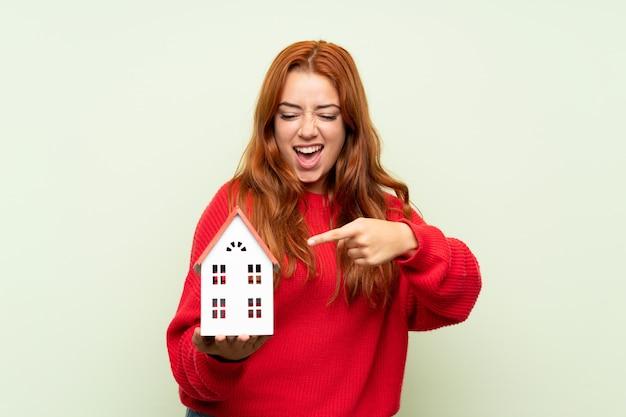 Chica pelirroja adolescente con suéter sobre pared verde aislado sosteniendo una casita