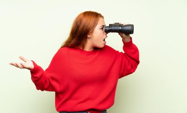 Chica pelirroja adolescente con suéter sobre verde aislado con binoculares negros