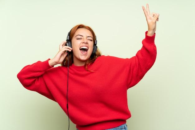 Chica pelirroja adolescente con suéter sobre verde aislado escuchando música con auriculares