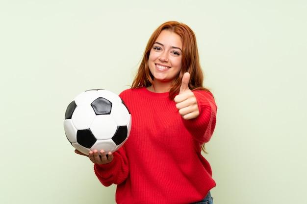 Chica pelirroja adolescente con suéter sobre verde aislado sosteniendo un balón de fútbol