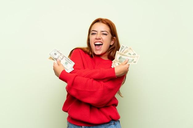 Chica pelirroja adolescente con suéter sobre verde aislado tomando mucho dinero