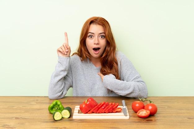 Chica pelirroja adolescente con verduras en una mesa con expresión facial sorpresa