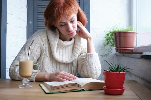 Chica pelirroja adulta joven relajante en casa con bebida caliente y libro