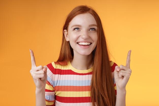 Chica pelirroja alegre feliz divirtiéndose en el parque de atracciones riendo alegremente apuntando hacia arriba con los dedos índice hacia arriba disfrutar de entretenimiento permanente fondo naranja divertido sonriendo con alegría