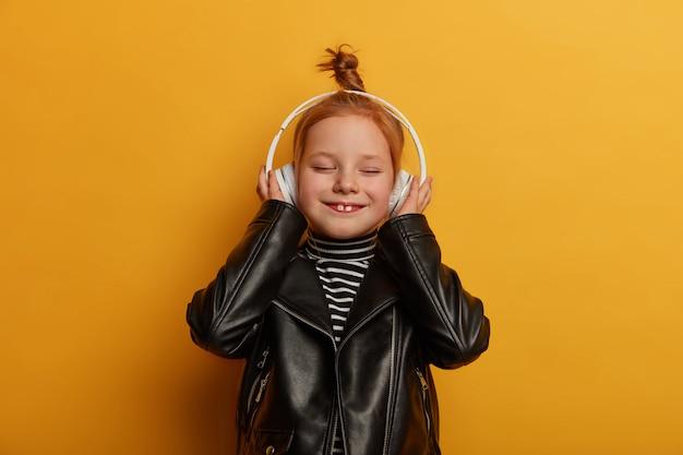 La chica pelirroja alegre muestra dos dientes, escucha música en auriculares, se viste con chaqueta de cuero, cierra los ojos con placer, pasa el tiempo libre sola, aislada sobre una pared amarilla. niños, entretenimiento