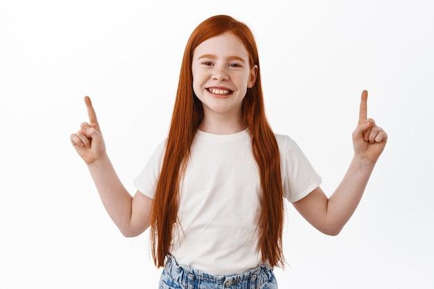 Chica pelirroja alegre sonriendo con dientes y apuntando con el dedo hacia arriba. niño de jengibre con pecas feliz mostrando publicidad, pared blanca