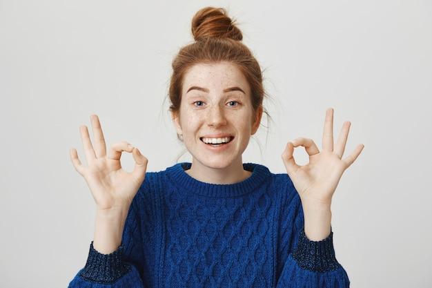 Chica pelirroja alegre sonriendo, mostrando bien en aprobación, asegura que todo está bien
