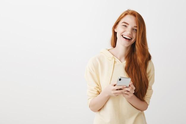 Chica pelirroja alegre sonriendo y riendo, con smartphone
