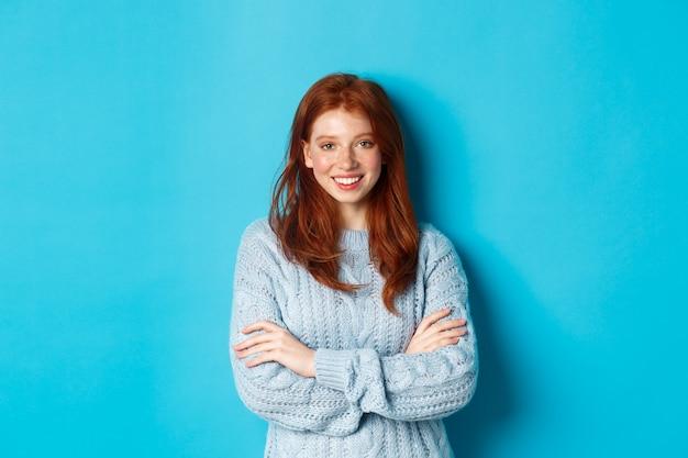 Chica pelirroja atractiva en suéter sonriendo y mirando a cámara, de pie confiado contra el fondo azul.