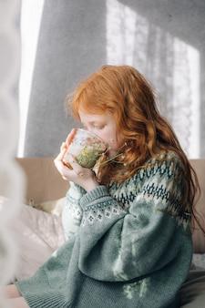 Chica pelirroja bebe su café de la mañana en un vaso de vidrio.