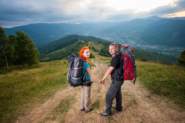 Chica pelirroja y chico tomados de la mano y mirando a la cámara en la carretera en la montaña en el fondo de las poderosas montañas, bosques, colinas y nubes ajardinadas cielo