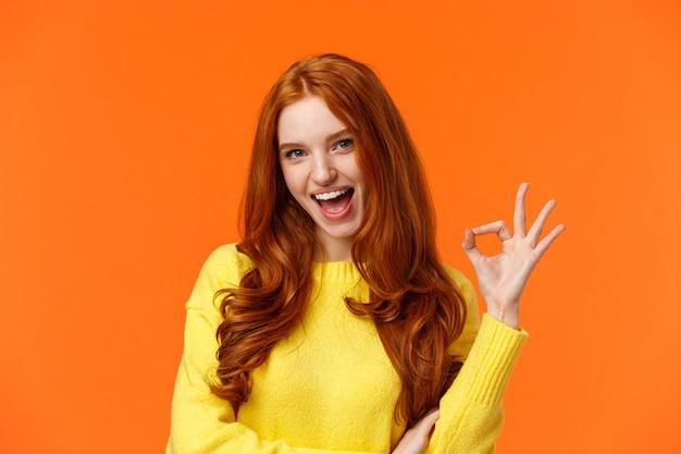 Chica pelirroja descarada y atrevida con rizos, mostrando un gesto excelente y sonriente y emocionada