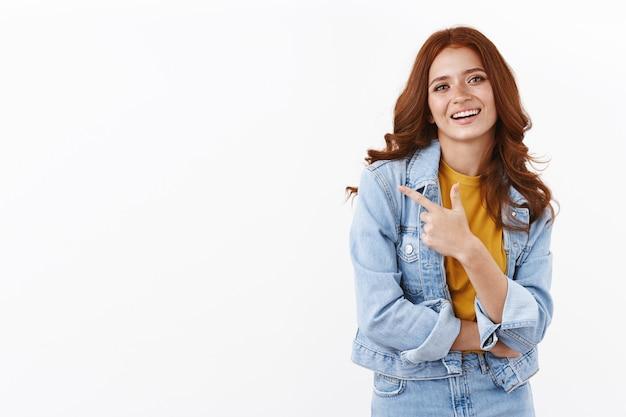 Chica pelirroja elegante con chaqueta vaquera, apuntando con el dedo hacia la izquierda y sonriendo confiada, dando consejos, sugiriendo promo, indicando espacio de copia lateral, de pie en la pared blanca alegre y decidida
