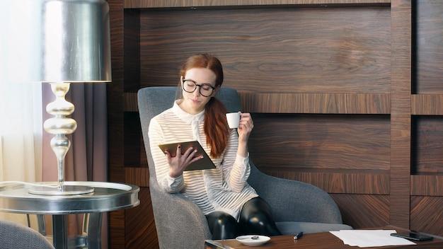 Chica pelirroja elegante trabajando en la oficina en casa